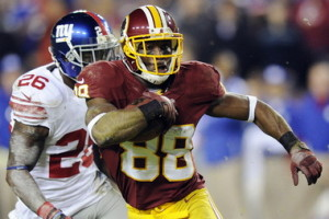 Washington Redskins wide receiver Pierre Garcon (88) carries the ball as New York Giants' Antrel Rolle gives chase during the first half of an NFL football game in Landover, Md., Monday, Dec. 3, 2012. (AP Photo/Nick Wass)